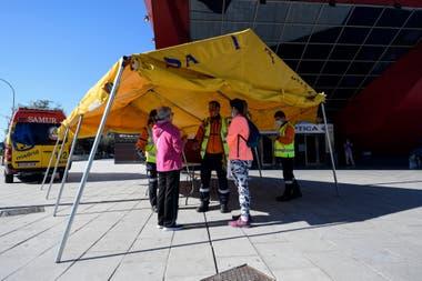 Miembros del Servicio de Emergencias Médicas de Madrid bajo una carpa frente a un centro de información en Madrid