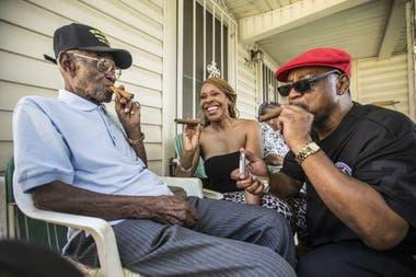 Richard Overton, a la izquierda, fuma un cigarro con algunos amigos del vecindario Donna Shorts, en el centro y Martin Wilford el domingo 3 de mayo de 2015 en Austin, Texas.