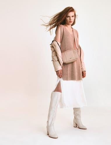 Campera puffer (Perramus), chaleco tejido (Giesso), vestido midi con tajo lateral, botas bucaneras de cuero con taco, cartera bandolera (Prüne)