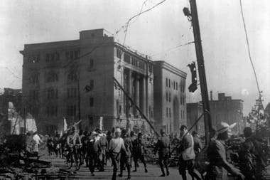 Soldados y civiles deambulan por las calles, al fondo se ve el Banco de Hiroshima