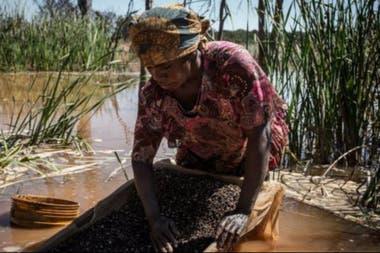 Una mujer separa cobalto del barro y rocas cerca de una mina en la RDC