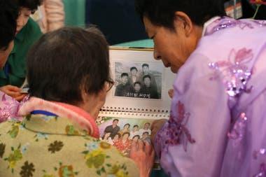 La surcoreana Han Shin-ja de 99 años mira fotografías junto a su hija de 672 años que vino de Corea del Norte