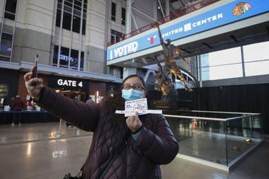 Una votante se saca una selfie después de emitir su voto frente a una estatua de Michael Jordan en el United Center, en Chicago, Illinois.