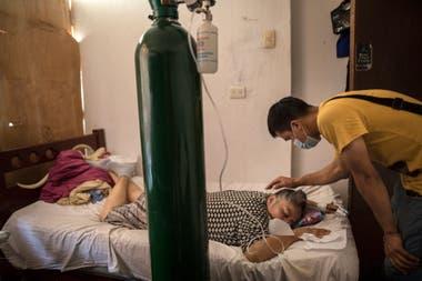 Elena Ruiz, de 53 años, está inhalando oxígeno como parte de su terapia de recuperación de COVID-19, mientras que su hijo Anthony está en Lima, Perú.