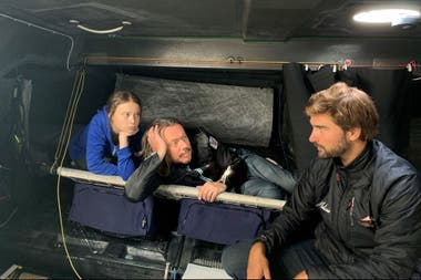 La activista climática sueca Greta Thunberg, su padre Svante y el comandante Boris Herrmann se sientan a bordo del yate Malizia II, que transportará a Thunberg a través del Atlántico para la Conferencia de Acción Climática de la ONU