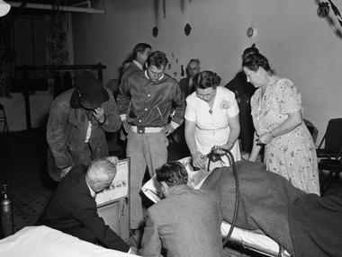 Los bomberos voluntarios y las enfermeras del pueblo, asistiendo a los enfermos con tanques de oxígeno el 30 de octubre de 1948 (National Geographic)