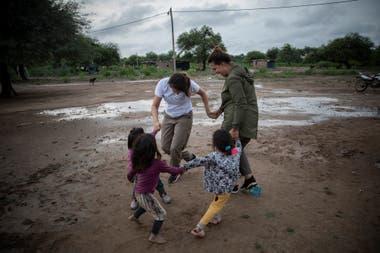 Dos voluntarias de la ONG Pata Pila juegan con niños de la comunidad El Cañaveral 1