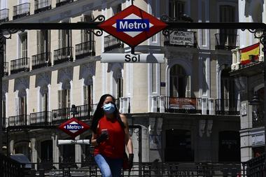 Una mujer camina con barbijo por la Puerta del Sol, una plaza de la ciudad española de Madrid, en medio de la pandemia de coronavirus