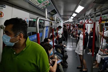 Los pasajeros usan mascarillas mientras viajan en el metro en Hong Kong el 29 de julio de 2020, después de que entraron en vigencia nuevas medidas de distanciamiento social