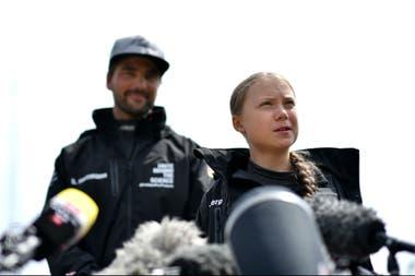 La activista climática sueca Greta Thunberg, acompañada por el capitán alemán del velero Malizia II, Boris Herrmann, habla durante una conferencia de prensa en el Mayflower Marina en Plymouth, suroeste de Inglaterra hoy, antes de su viaje