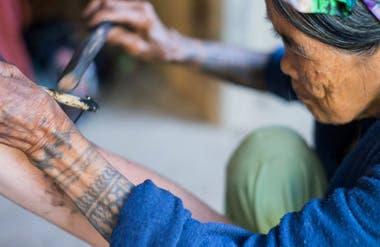Whang Do concentrada en su labor, tatuando el brazo de uno de los tantos turistas que llegan hasta su pueblo para tatuarse con ella.