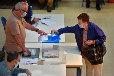 Una mujer con una máscara facial emite su voto en un colegio electoral en San Sebastián, durante las elecciones regionales vascas, el 12 de julio de 2020