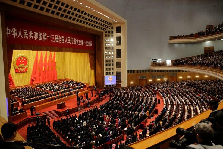 Los líderes y delegados chinos se ponen de pie mientras se toca el himno nacional en la sesión de apertura de la Asamblea Popular Nacional anual en el Gran Salón del Pueblo en Beijing