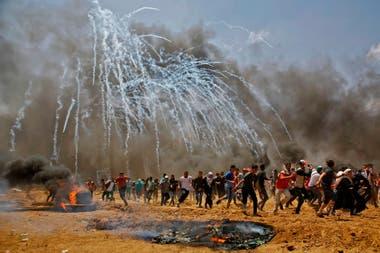 Los palestinos huyen de los gases lacrimógenos lanzados por Israel