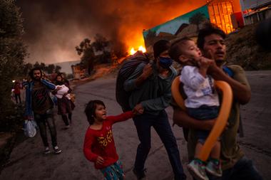 En esta foto de archivo tomada el 9 de septiembre de 2020 una familia de migrantes abandona el campamento de Moria después de que estallara un incendio en la isla de Lesbos