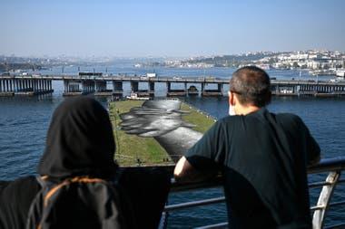 Los más curiosos se acercaron al puente para ver cómo la obra de arte flotante navegaba por el río