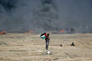 Un hombre sostiene una bandera palestina durante los enfrentamientos con las fuerzas israelíes cerca de la frontera entre la franja de Gaza e Israel