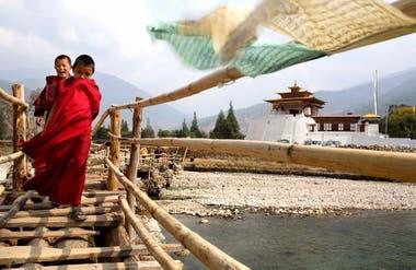 Jóvenes monjes cruzan el puente de madera y bambú que va desde el Dzong hasta el pueblo de Punakha, al otro lado del río.