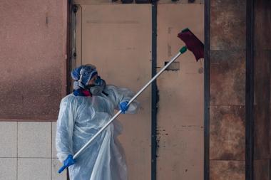 Un trabajador de limpieza desinfecta el sector de ambulancias afuera de un hospital en Santiago, el 6 de julio de 2020, en medio de la pandemia de coronavirus