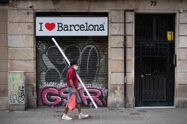 Un hombre con mascarilla pasa frente a una tienda cerrada en el centro de Barcelona el 12 de agosto de 2020