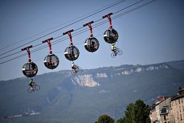 Un grupo de ciclistas cuelga bajo los teleféricos de Grenoble Bastille
