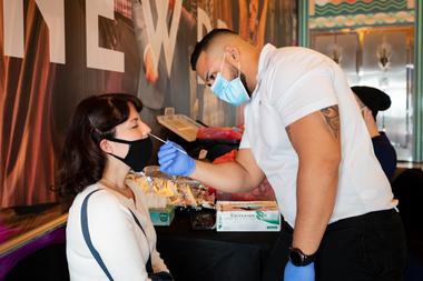 """Una persona se hace la prueba de Covid-19 antes de participar en la obra """"Seven Deadly Sins"""" en Lincoln Road en Miami Beach, Florida, el 23 de diciembre de 2020"""