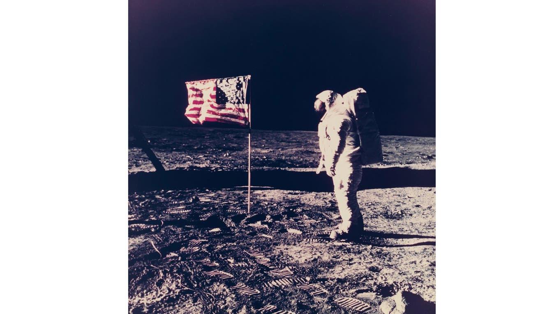 Aldrin junto a la bandera norteamericana, montada en un tubo de plástico. Los cables, abajo a la izquierda, pertenecen a la cámara de televisión. Foto: NASA