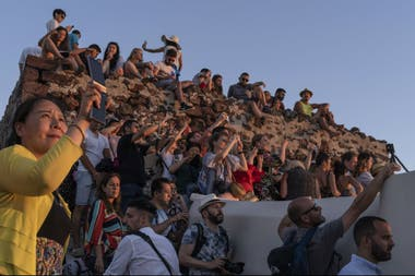 Un grupo de turistas sobre las ruinas del castillo de Oia captura imágenes de su famosa puesta de sol