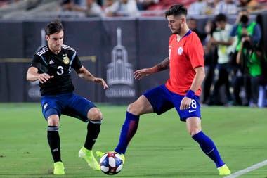 Nicolás Tagliafico intenta quitarle la pelota a Ángelo Sagal, durante el partido entre la Argentina y Chile.