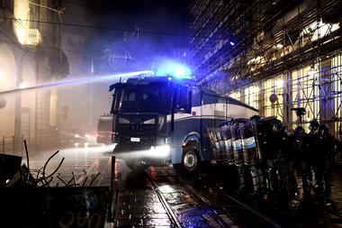 Agentes de la policía italianos utilizan un cañón de agua durante una protesta de activistas de extrema derecha contra las medidas de restricción del gobierno para frenar la propagación del coronavirus, en el centro de Turín, el 26 de octubre de 2020