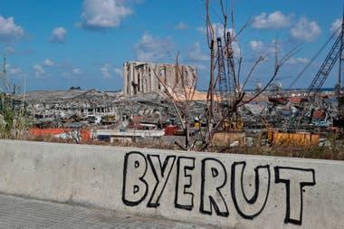 Fotografía tomada el 9 de agosto de 2020 muestra un graffiti en la pared de un puente que domina el puerto de Beirut, el lugar de la explosión que mató al menos a 154 personas y devastó zonas de la capital.