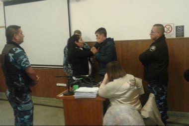 Los policías observan con atención el inusual gesto de la mujer con el victimario de su hijo