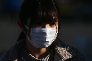 Una joven usa un barbijo en Pekín