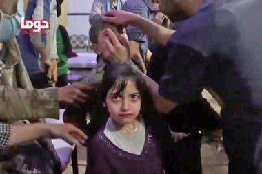 Los socorristas revisan a los niños que fueron afectados por el ataque pero que lograron sobrevivir