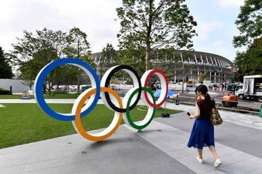 Una postal de los anillos de los Juegos Olímpicos. De fondo, el nuevo estadio Nacional de Tokio