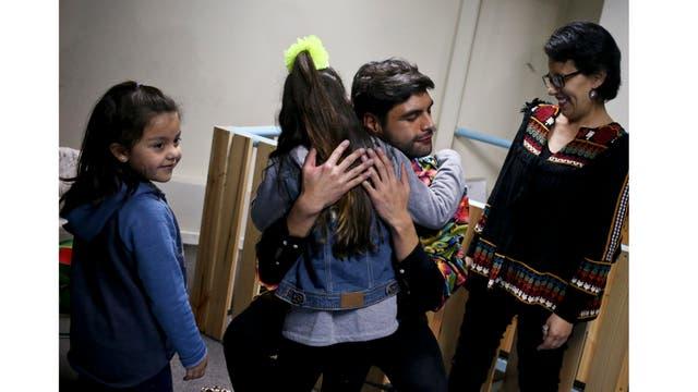 Selenna abraza a un narrador al final de su lectura junto a su amiga transexual Mathilda, en una librería en Santiago, Chile