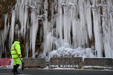 Un trabajador vial observa las rocas congeladas al lado de la ruta al norte de España