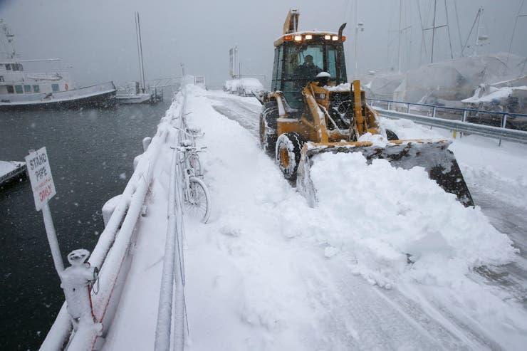 Una máquina quita la nieve de un muelle en una marina de Boston