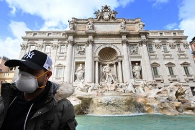 Un turista con barbijo, ante la emblemática Fontana di Trevi, en Roma