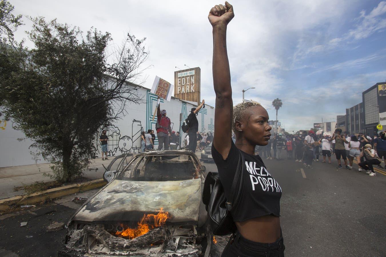 Una manifestante frente a un auto de policía en llamas en Los Ángeles, el 30 del mes pasado