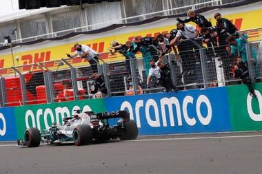 Tarea cumplida: Lewis Hamilton cruza la meta en el Gran Ptremio de Hungría y los mecánicos festejan desde el enrejado el éxito del piloto británico