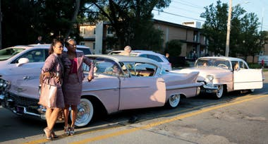 El coche fúnebre fue flanqueado por varios Cadillac rosas
