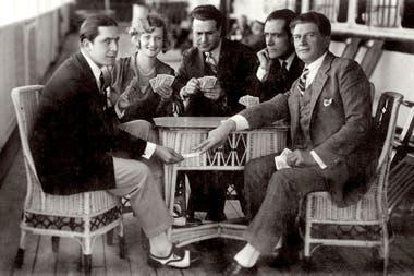 Carlos Gardel juega a las cartas con sus amigos Marguerite Vignou, Victor Damiani, Jose A.Ganduz y Adamo Diduv, a bordo del buque Conte Rosso, el 12 de junio de 1928