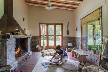 Guadalupe trabaja en su nueva muestra frente al enorme hogar del living. Pufs con fundas de telar y manta (Illari, de Magdalena Sánchez de Bustamante). En el rincón, lámpara de resina (Sariri, Jujuy).