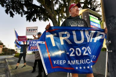 Un seguidor de Donald Trump sostiene una bandera en Jacksonville, Florida
