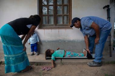 Una asistente de salud de la comunidad Misión La Paz toma medidas de talla y peso