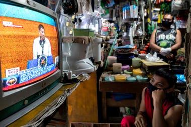 Ciudadanos observan al presidente de Filipinas, Rodrigo Duterte, ayer durante su mensaje en la Cámara de los Representantes