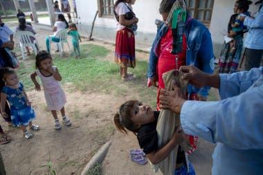 Uno de los asistentes de salud de la comunidad Misión La Paz toma medidas de talla y peso a una niña. Todos los miércoles, el equipo de Pata Pila atienden a los niños y las niñas de las comunidades de la zona.
