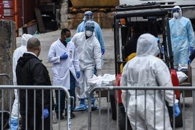 Los trabajadores médicos llevan un cuerpo a un camión refrigerado afuera del Hospital de Brooklyn el 31 de marzo de 2020 en la ciudad de Nueva York. Debido a un aumento en las muertes causadas por el Coronavirus, los hospitales están utilizando camiones refrigerados como morgues de turno.
