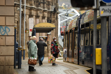 Los viajeros usan tapabocas mientras esperan en una parada de tranvía en Sheffield, South Yorkshire, el 21 de octubre de 2020, antes de que entren en vigor nuevas medidas de bloqueo a medida que aumenta el número de casos de coronavirus